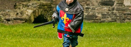 Image: Boy dressed as a knight charging forward at Beaumaris Castle in Wales